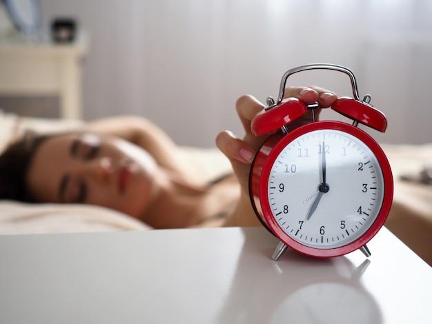 Żeńska ręka wyłącza przeszkadzający hałaśliwy alarm od czerwonego budzika