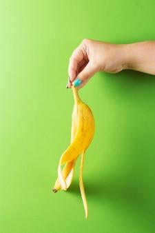 Żeńska ręka z kolorowym manicure'u mieniem obrał banana na zielonym tle