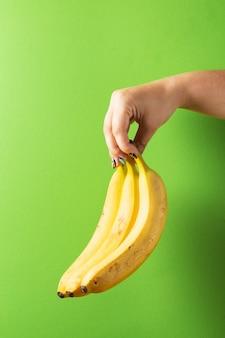 Żeńska ręka z kolorowymi manicure u mienia bananami na zielonym tle