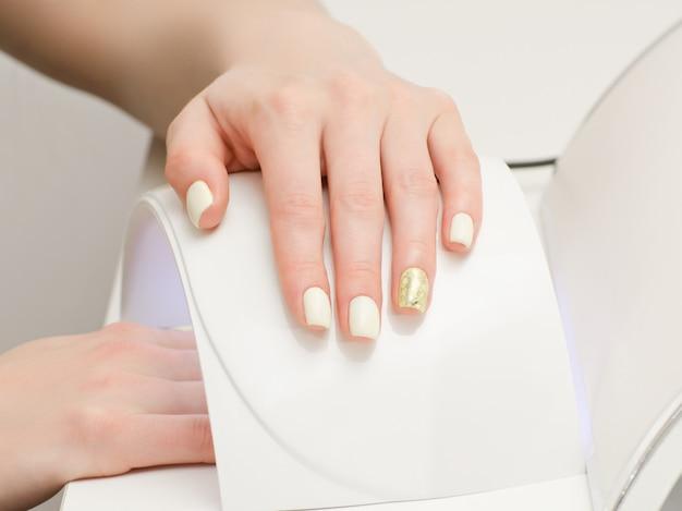 Żeńska ręka z manicure em na bielu