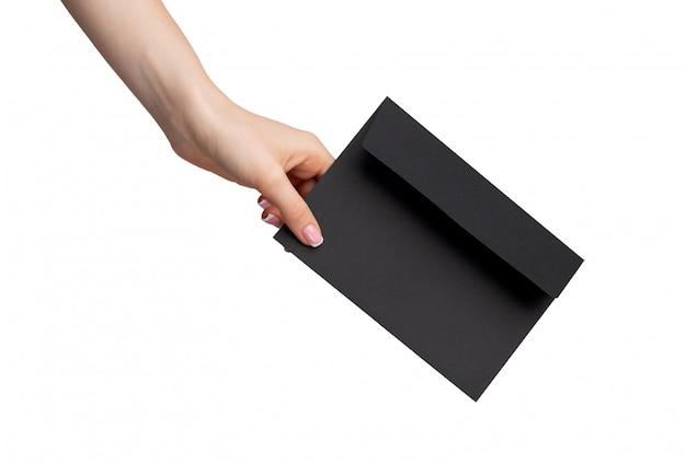 Żeńska ręka z manicure'u mienia kopertą odizolowywającą na białym tle