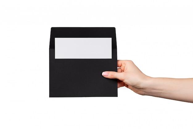 Żeńska ręka z manicure'u mienia kopertą odizolowywającą na bielu