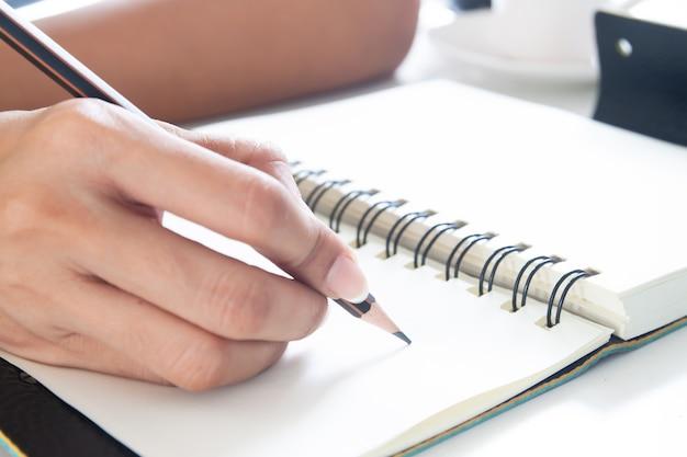 Żeńska ręka z ołówkowym writing na notatniku, zamyka w górę strzału