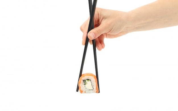 Żeńska ręka z pałeczkami trzyma suszi rolkę, odosobnioną na biel powierzchni