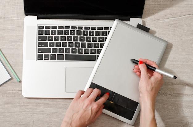 Żeńska ręka z rysikiem na graficznej pastylce, laptop otwarty na lekkim stole, odgórny widok