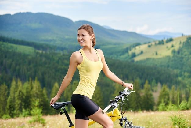 Żeńska rowerzysta pozycja na trawiastym wzgórzu z żółtym halnym bicyklem, cieszy się letniego dzień w górach