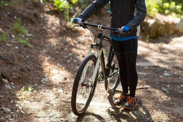 Żeńska rowerzysta pozycja z rowerem górskim na drodze polnej