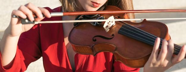 Żeńska skrzypaczka bawić się z instrumentem i łękiem