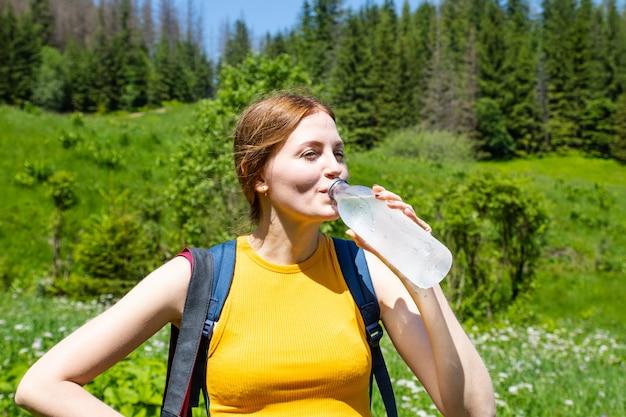 Żeńska turystyczna dziewczyna w żółtej koszulce i niebieskich dżinsach zwiera napój wodę z plastikowej butelki na zielonego lasu
