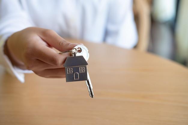 Żeński agent nieruchomości ręki mienia domu klucz, nieruchomości pojęcie.