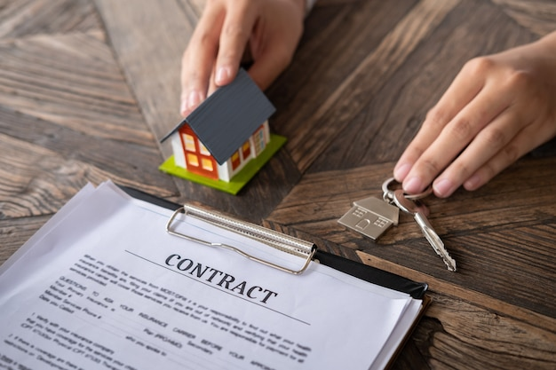 Żeński agent nieruchomości ręki mienia domu model i domowy klucz z kontraktem na stole