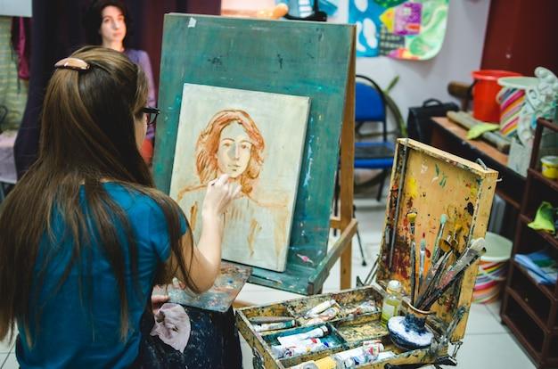 Żeński artysta maluje na płótnie na sztaludze w studiu sztuki
