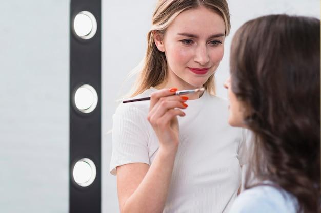Żeński artysta piękno stosuje makeup na modelu