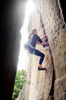 Żeński arywisty pięcie z arkaną na skalistej ścianie