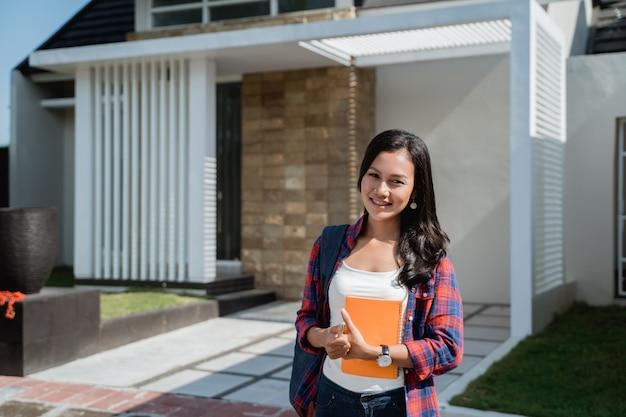 Żeński azjatykci uczeń przed jej domem