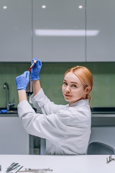 Żeński badacz medyczny lub naukowy patrzeje próbnej tubki w laboratorium.