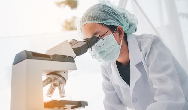 Żeński badacz medyczny patrzeje mikroskop w medycznym laboratorium. medyczna koncepcja eksperymentalna