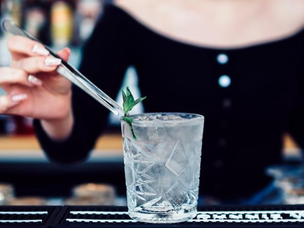 Żeński barman dekoruje koktajlu szkło