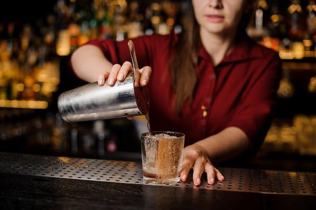 Żeński barman nalewa świeżego napój od shaker do szkła