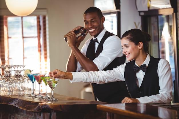 Żeński barman ozdabia koktajl z oliwką