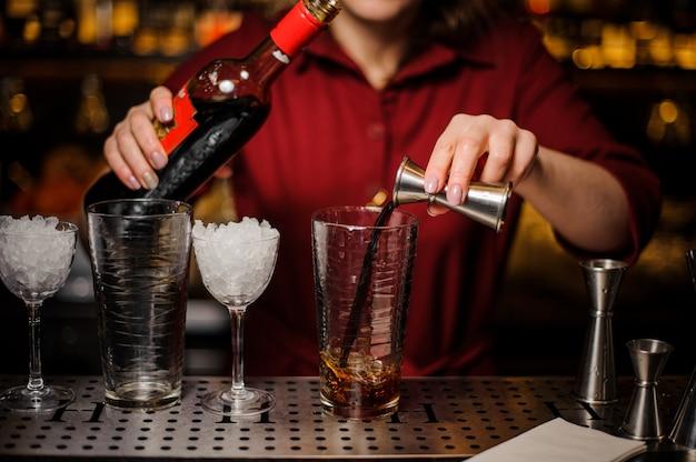 Żeński barman robi świeżemu i smakowitemu alkoholowemu koktajlowi