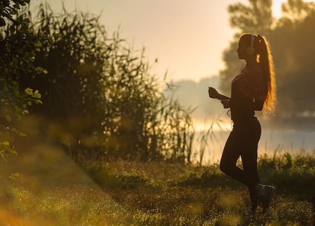 Żeński biegacz biega w naturze podczas wschodu słońca