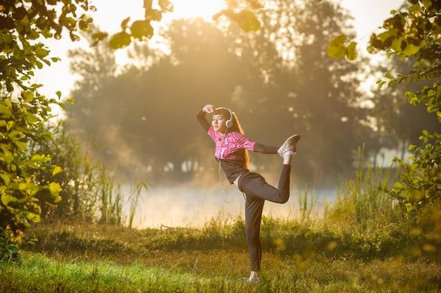 Żeński biegacza bieg w naturze podczas wschodu słońca