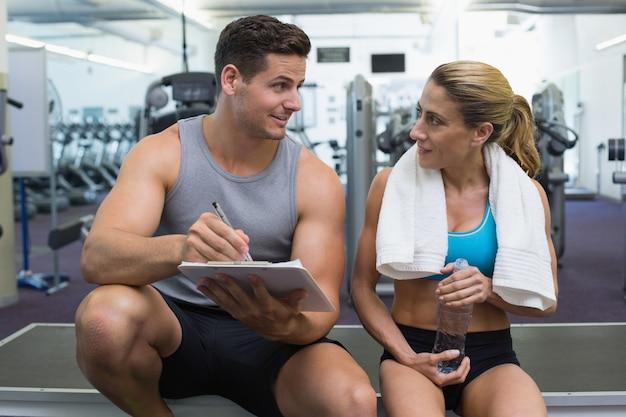 Żeński bodybuilder obsiadanie z osobistym trenerem opowiadać