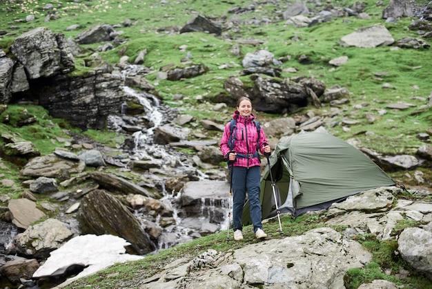 Żeński brunetka arywista chodzi z laskami w rękach w górę zielonego skalistego zbocza przed pięknymi skalistymi górami