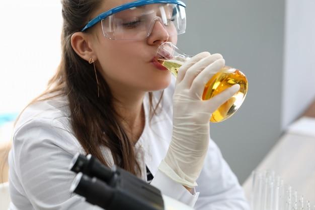 Żeński chimist w białych rękawiczkach ochronnych pije piwo z portretu probówki. koncepcja testu żywności