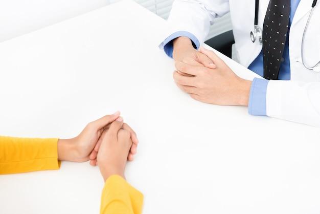 Żeński cierpliwy konsultować z lekarką przy stołem w biurze