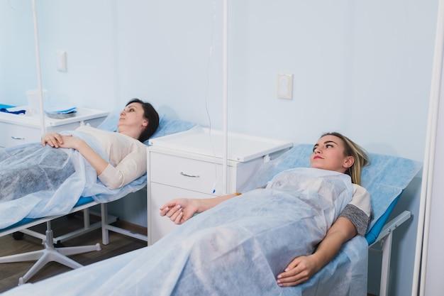 Żeński cierpliwy odpoczywać w łóżku medycznym przy szpitalnym oddziałem