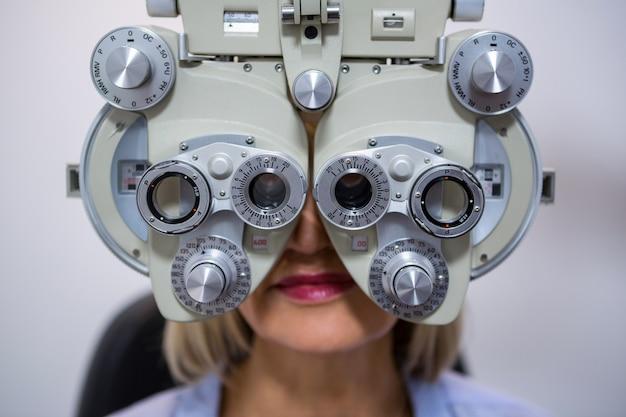 Żeński cierpliwy patrzeć przez phoropter podczas oko egzaminu