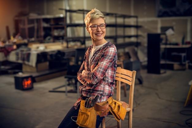 Żeński ciesielka pracownik z narzędziami opiera przeciw krzesłu i pozuje, podczas gdy patrzejący daleki w warsztacie