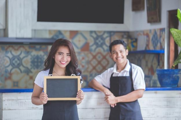Żeński cukierniany pracownik uśmiecha się pustego blackboard i trzyma