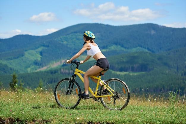 Żeński cyklista jedzie na żółtym bicyklu