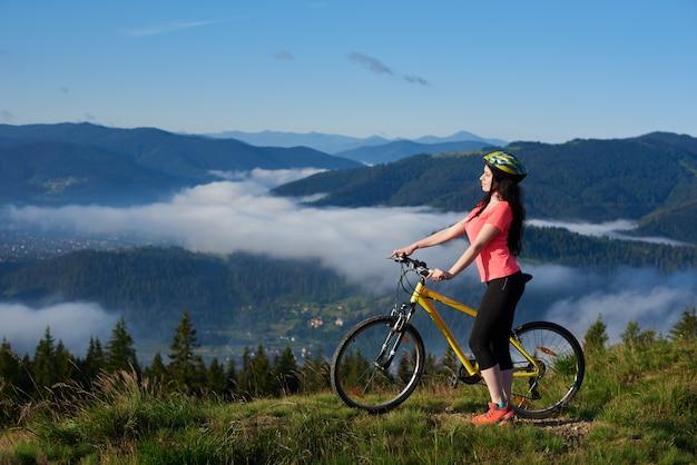 Żeński cyklista jedzie rower w góry