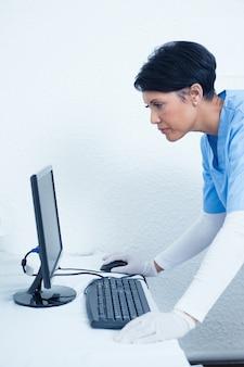 Żeński dentysta patrzeje komputerowego monitoru