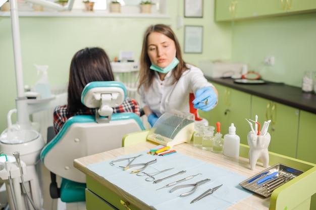 Żeński dentysta pracuje przy stomatologiczną kliniką z żeńskim patien