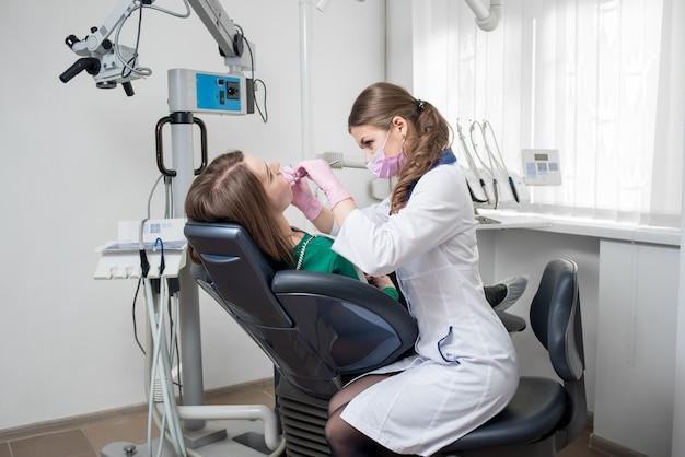 Żeński dentysta z stomatologicznymi narzędziami sprawdza w górę cierpliwych zębów przy stomatologicznym kliniki biurem