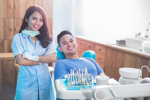 Żeński dentysta z szczęśliwym męskim pacjentem przy kliniką