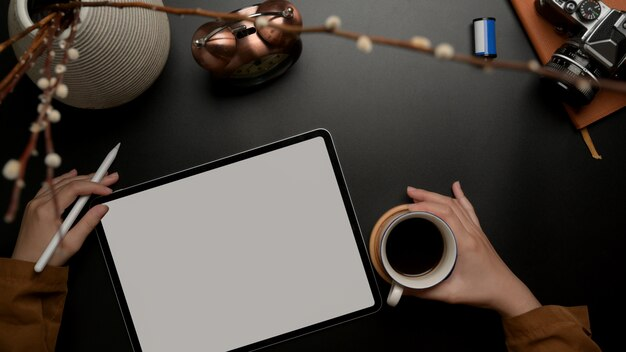 Żeński działanie z pustego ekranu pastylką podczas gdy prawa ręka trzyma filiżankę na biurowym biurku