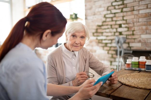 Żeński emeryt używa pastylkę podczas gdy siedzący blisko opiekuna