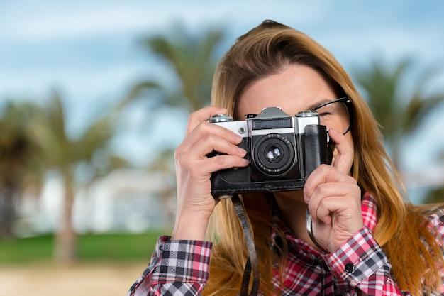 Żeński fotograf trzyma rocznik kamerę