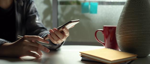Żeński freelancer używa smartphone podczas gdy siedzący przy stolik do kawy obok okno w żywym pokoju