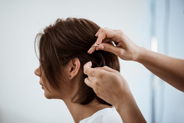 Żeński fryzjer robi fryzurze brunetki kobieta w salonie piękności