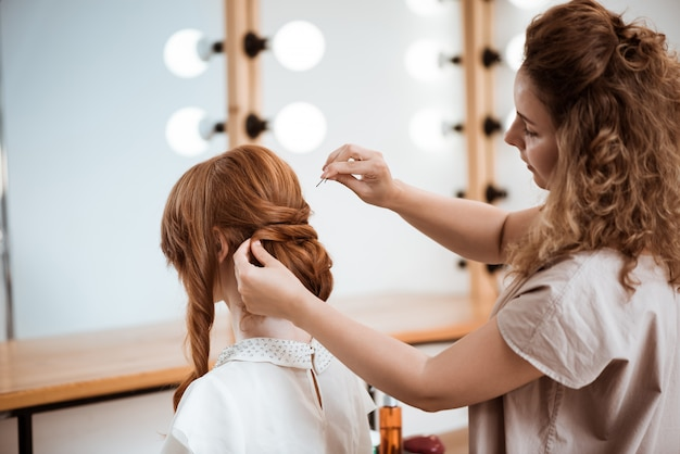 Żeński fryzjer robi fryzurze rudzielec kobieta w salonie piękności