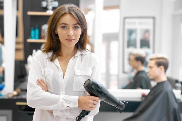 Żeński fryzjer utrzymuje suszarka do włosów patrzeje kamerę, pozuje w beaty salonie.
