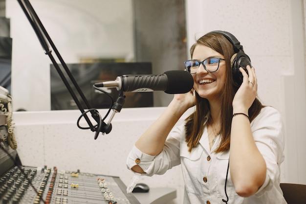 Żeński gospodarz komunikujący się przez mikrofon. kobieta w studio radiowym.