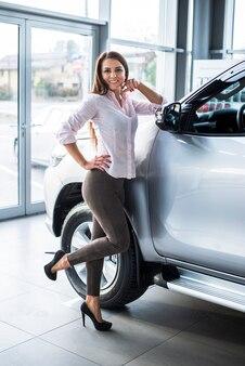 Żeński handlowiec samochodowy pozuje obok samochodu
